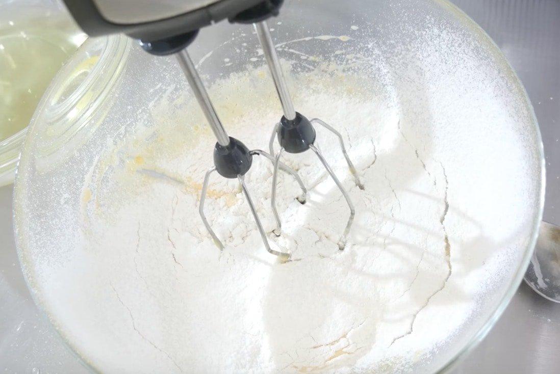 Желтки взбить с 30 г сахара, просеять муку с разрыхлителем и перемешать.