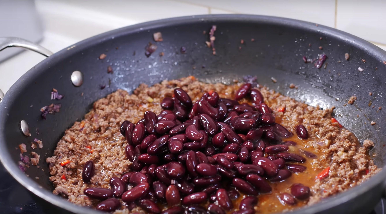 Вливаем соус к фаршу и добавляем консервированную фасоль, предварительно слив жидкость