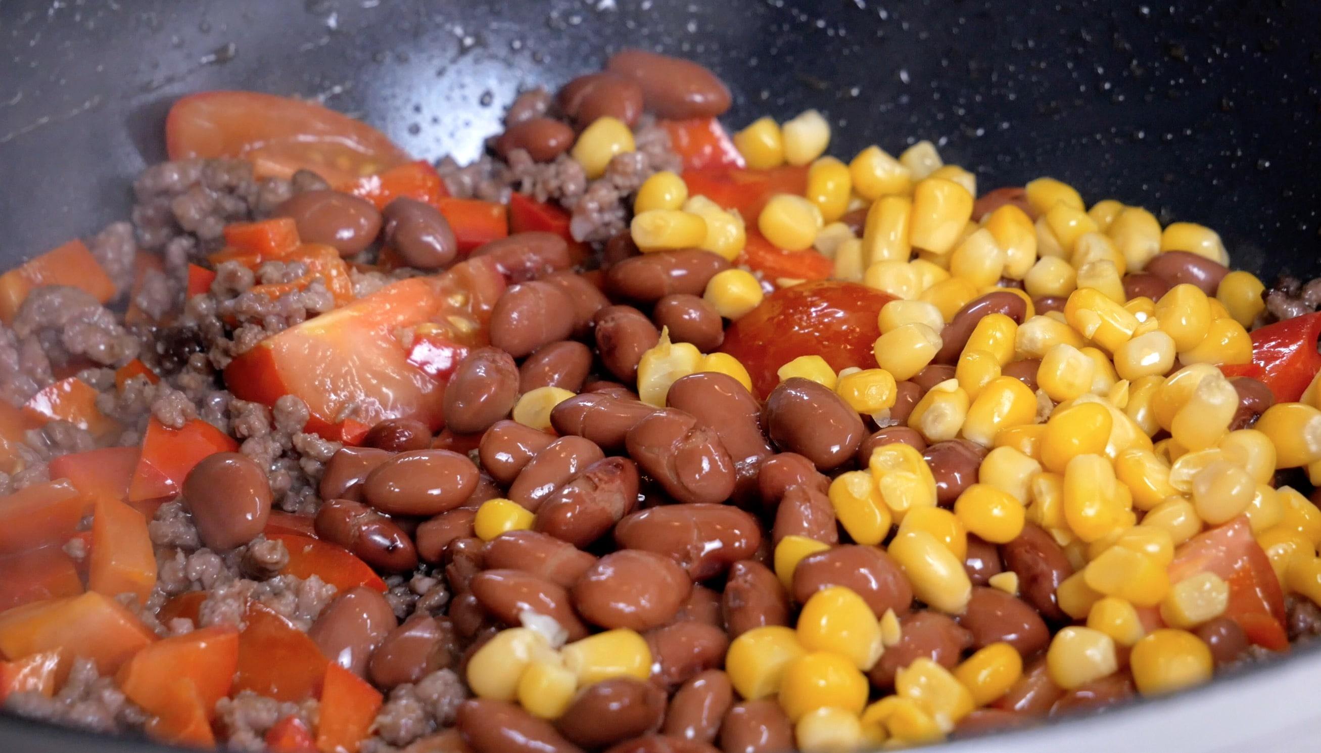 Добавляем свежие овощи, лук, фасоль, кукурузу. Обжариваем пару минут